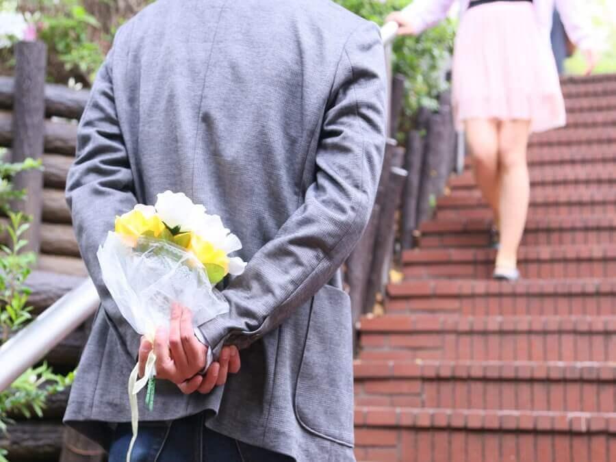 花束を持って待つ男性
